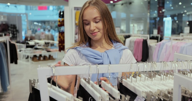 コロナウイルスとパンデミックのために検疫が解除された後、かわいい女の子が店の棚で服を選んでいます。