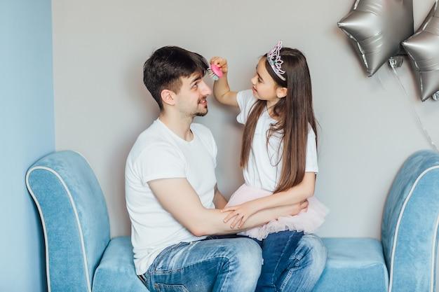 Красивая девушка делает волосы своего отца