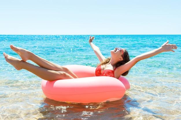 예쁜 여자는 바다에 분홍색 풍선 반지에 재미있다