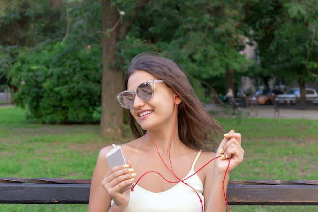 Pretty girl is listening to music in headphones outside.