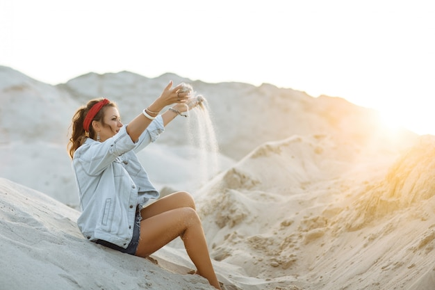 A pretty girl in jeans, short shorts, a red hoop and a white bra is sitting on the sand