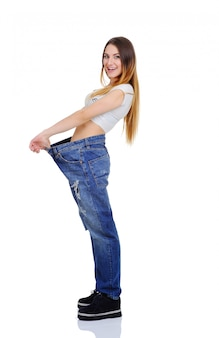 Pretty girl jeans with large size enjoys a slim figure. weight loss. slim girl in a loose fitting on a white background