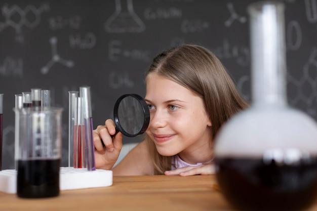 Bella ragazza che impara di più sulla chimica in classe
