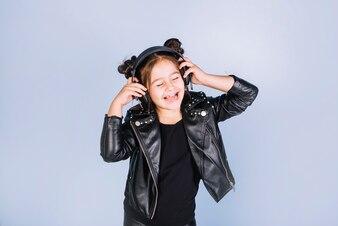 Pretty girl listening music on headphone standing against blue backdrop