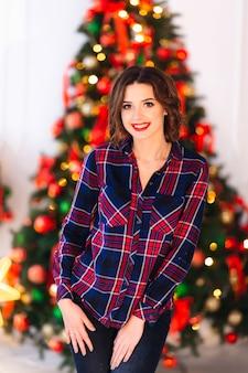 かわいい女の子がカメラのレンズを見て、クリスマスツリーの背景に微笑む
