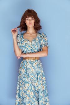 かわいい女の子は手夏服で髪を持って楽しみにしています