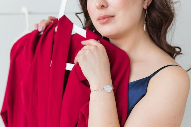 適切なものを選択しながらドレスを見ているかわいい女の子。ファッション、販売、店舗のコンセプト。