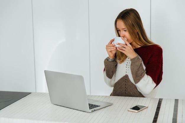 美しい女の子は、暖かいセーターを着て、コーヒーを飲む、ラップトップ画面を見て。家に。