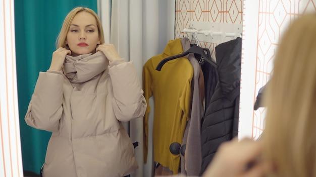 예쁜 여자는 탈의실에서 거울에 재킷을 찾습니다.