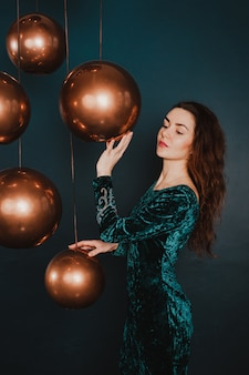 Pretty girl in luxury dress, playing with golden balls