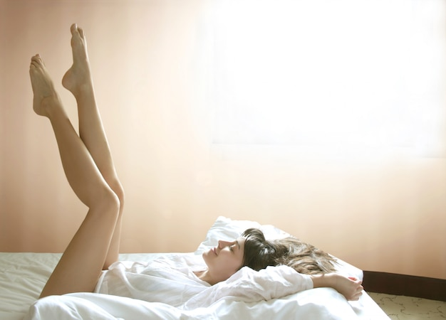 Pretty girl lying on her bed spreading legs