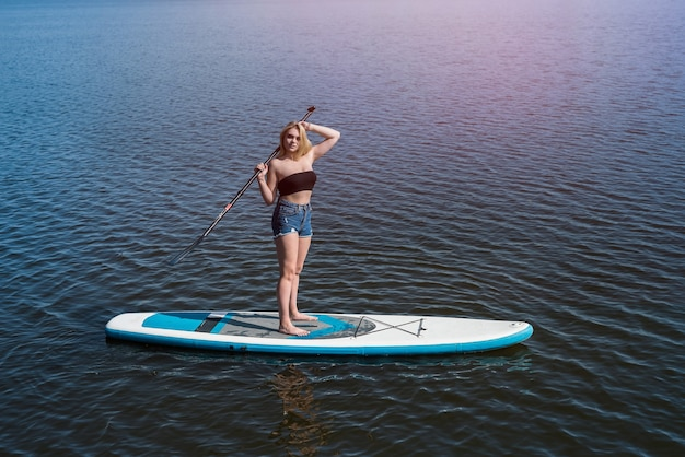 Pretty girl lying on paddle board on dark blue pond water. travel or vacation concept