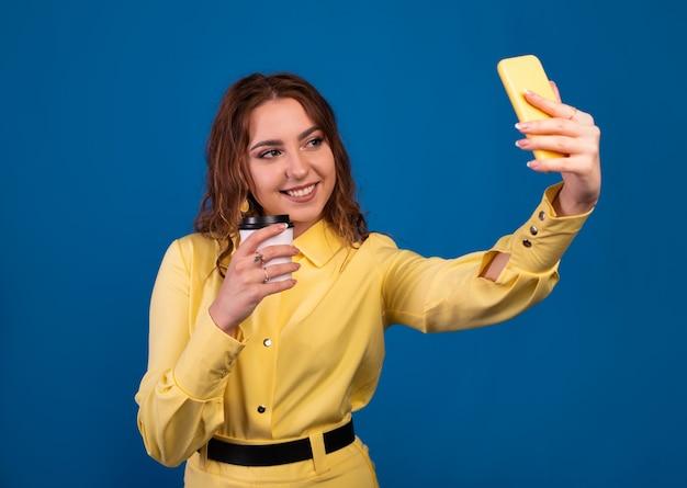 Красивая девушка корчит утиное лицо и сделает автопортрет на свой смартфон.