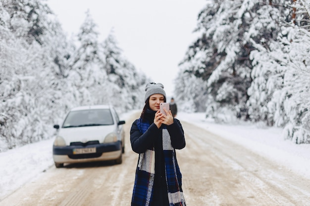 A pretty girl makes photographs on the phone in the middle of a snowy road