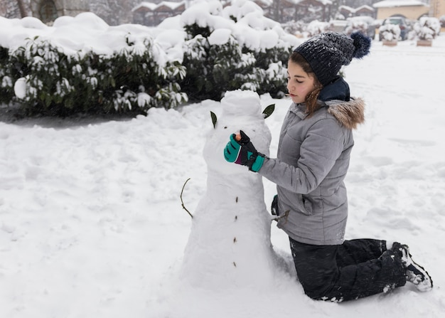 Pretty girl making snowman during winter season
