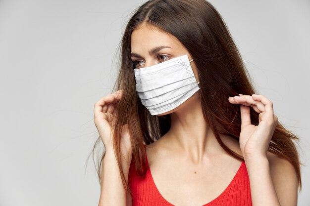 Красивая девушка в медицинской маске смотрит в сторону руки возле лица крупным планом