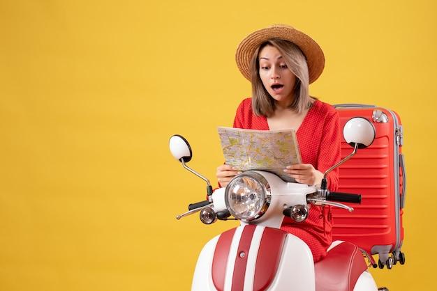 Bella ragazza in motorino con valigia rossa che tiene mappa sorprendente