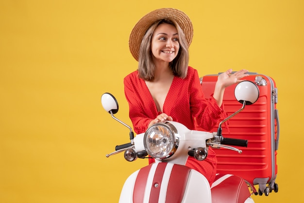 Bella ragazza sul motorino con la valigia rossa che punta a destra