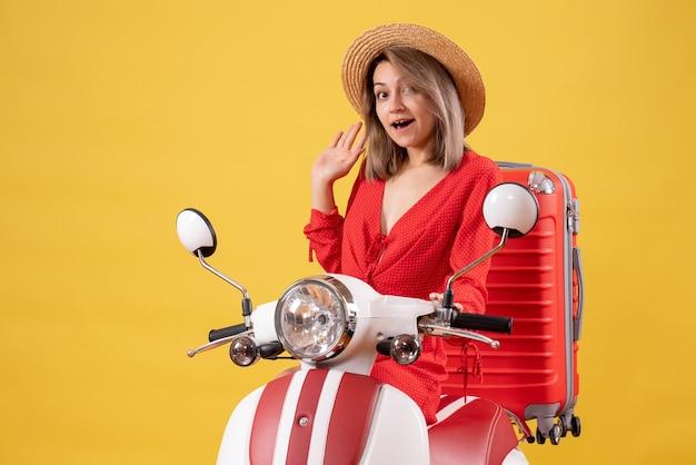 Bella ragazza in motorino con valigia rossa sorprendente