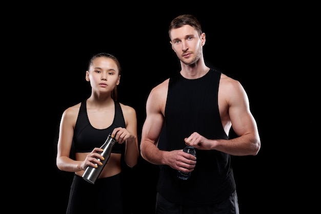 Pretty girl and muscular sportsman in activewear holding bottles with water while going to drink after training in gym
