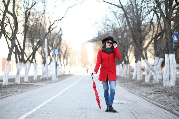 Красивая девушка на прогулке с красным зонтиком в городе