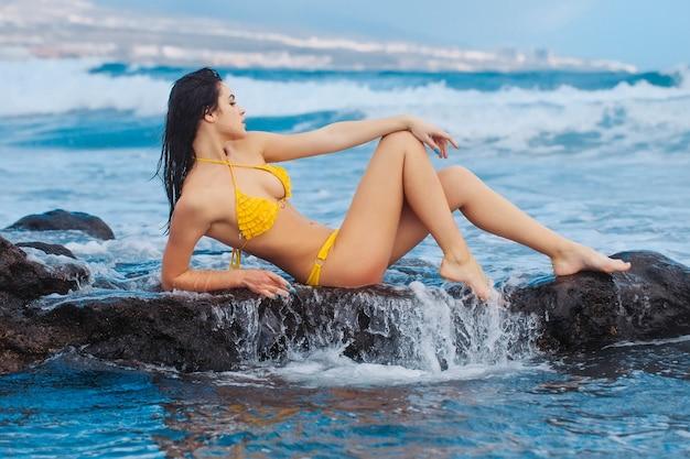 Красивая девушка или красивая женщина, сексуальная стройная модель, в сексуальном желтом купальнике, сидит в брызгах воды на скалах на пляже на открытом воздухе в солнечный летний день на фоне синего моря