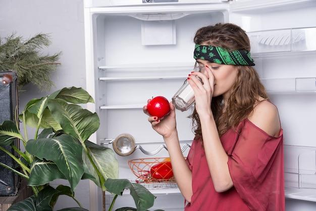 Красивая девушка или сексуальная женщина-хиппи с милым лицом в зеленом носовом платке или бандане на вьющихся волосах возле холодильника, растительный напиток из стекла и держит красное яблоко