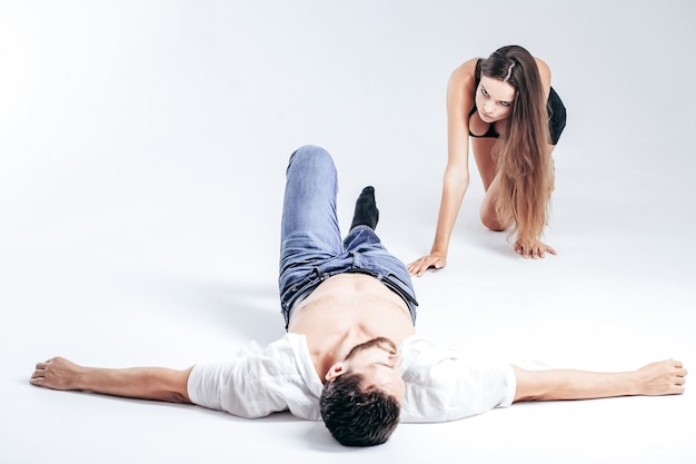 Красивая девушка или сексуальная женщина с длинными волосами брюнетки в черной майке ползет на коленях к бородатому мужчине или жестокому кавказскому хипстеру в рубашке с голым торсом, лежащим на полу, изолированном на белом фоне