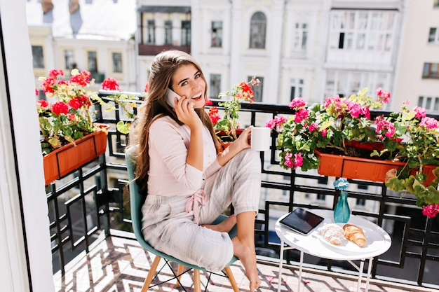 Pretty girl in pajama having breakfast on balcony in the sunny morning. she holds a cup, speaking on phone smiling .