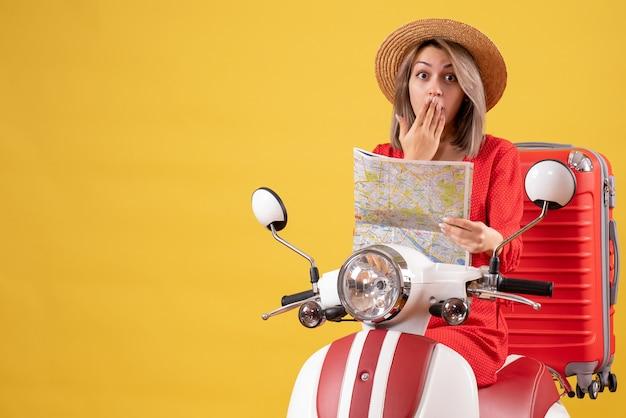 Bella ragazza con cappello panama sul motorino con mappa rossa della tenuta della valigia suitcase