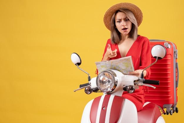 Bella ragazza con cappello panama sul motorino con valigia rossa guardando la mappa