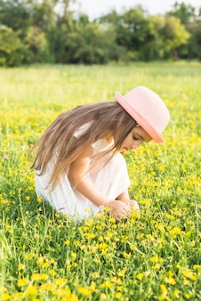 Pretty girl picking yellow flowers in the field