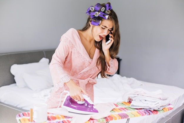 Pretty girl in pink bathrobe and curler ironing clothes and speaking on phone at home. she looks astonished and busy.