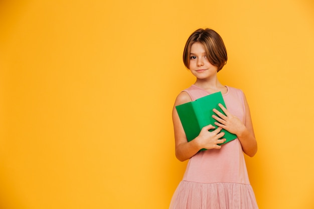 Pretty girl in pink dress holding green book isolated