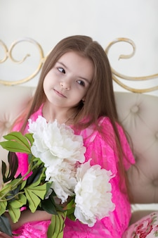 Pretty girl in pink dress with white peonies