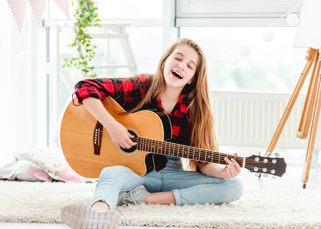 Красивая девушка играет на гитаре, сидя на полу