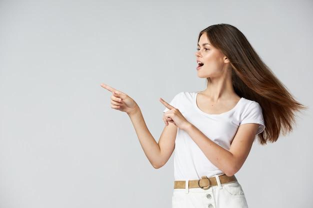 サイドの感情に指を指すかわいい女の子の長い髪の白いtシャツのトリミングビュー