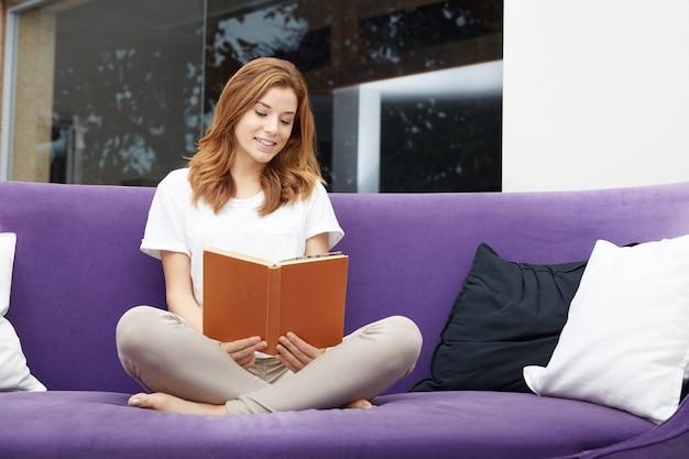 Pretty girl reading a book on purple sofa