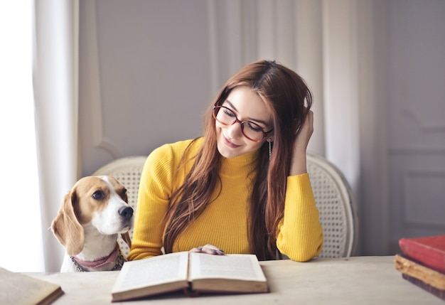 Pretty girl reading with her dog