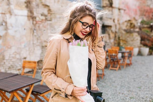 かわいい女の子が思いがけない贈り物を受け取って、紙袋に花を持って混乱して笑いました。屋外カフェでポーズをとるチューリップの花束とメガネとベージュのジャケットで恥ずかしい若い女性。