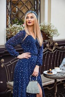 Красивая девушка расслабиться в кафе. утренний кофе. сексуальная блондинка с макияжем. готов к свиданию. красота и мода. девушка носить украшения для волос ободок. модная женщина обруч для волос с драгоценным камнем.