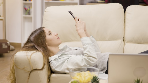 スマートフォンを使ってソファでくつろぐ可愛い女の子。バックグラウンドで彼氏。