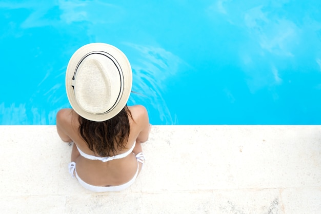 Pretty girl relaxing at the swimming pool in the summertime