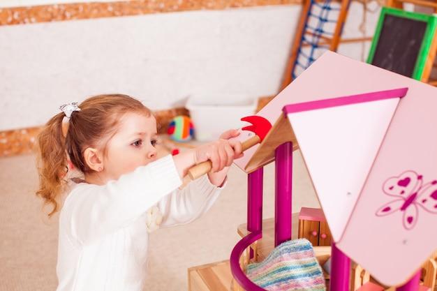 Красивая девушка ремонтирует крышу кукольного домика в детском саду