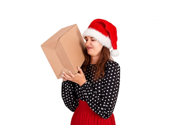 Pretty girl in santa hat is not happy and is disgusted her gift. isolated