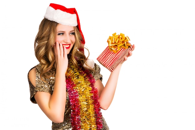 Pretty girl in santa hat with present on white background