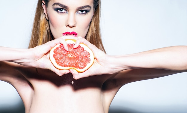 Pretty girl or sexy woman with stylish makeup on beautiful face squeezing juice from fresh orange grapefruit, citrus fruit with hands on grey background