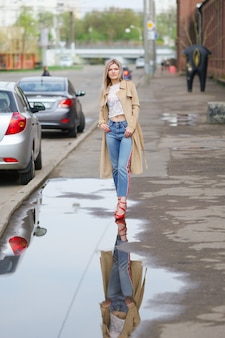 Pretty girl in short jeans and raincoat walking on the street after the rain