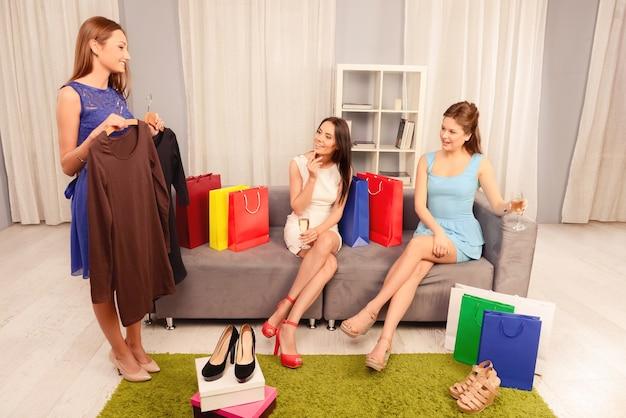 그녀의 친구에게 새 옷과 신발을 보여주는 예쁜 여자