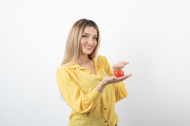 白地に赤いトマトを示すかわいい女の子。
